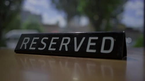 RESERVED sign placing on the cafe table with city view window.