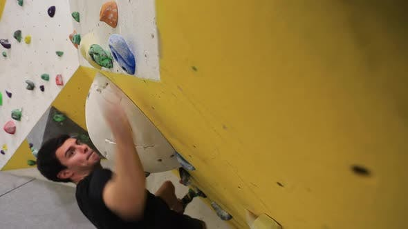 Thumbnail for Close-up of a mans hands has he climbs in an indoor climbing gym.