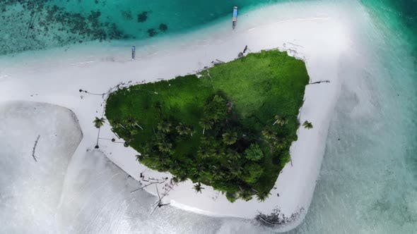 Thumbnail for Ungraded cinematic overhead aerial view of a beautiful small island beach in the middle of the ocean