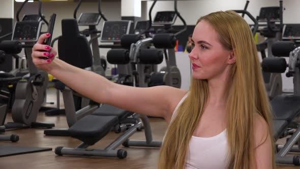 Thumbnail for Eine junge schöne Frau nimmt Selfies in ein Fitness-Studio