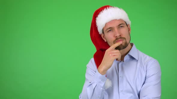 Thumbnail for A Young Handsome Man in a Christmas Hat Thinks About Something - Green Screen Studio
