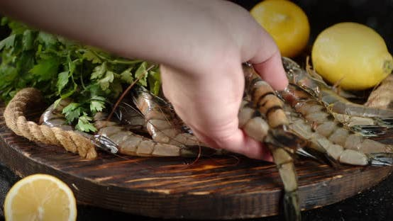Thumbnail for A Man's Hand Puts Raw Shrimp on a Wooden Tray