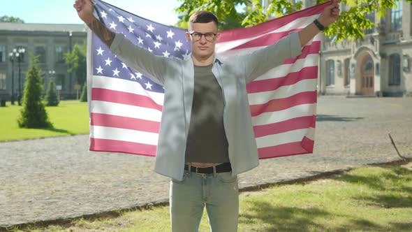 Thumbnail for Confident Young Man Spreading Hands Holding American Flag. Portrait of Handsome Intelligent