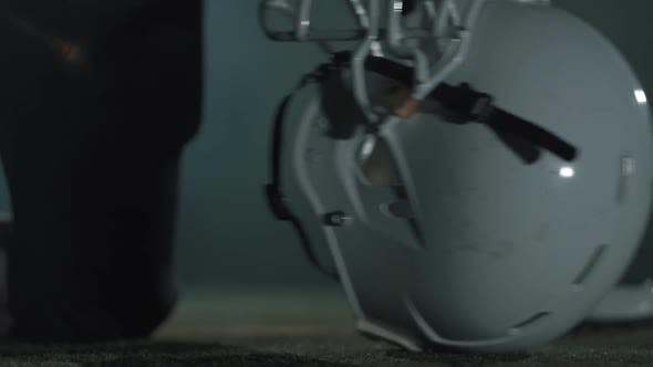 Thumbnail for Close-up Hands of American Football Player in Gloves Lying on His Helmet Before the Game Close Up