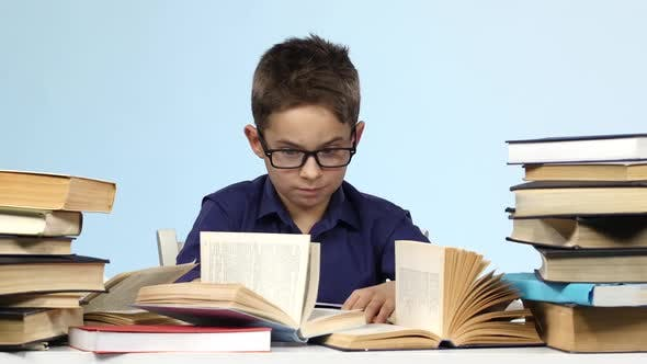 Boy with Glasses Sits at a Table and Excitedly That Is Looking For. Blue Background.