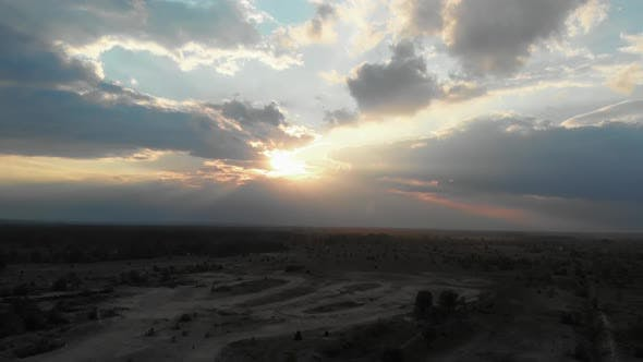 Thumbnail for Aerial View of a Beautiful Sunset in the Clouds Above the Forest in a Sandy Area