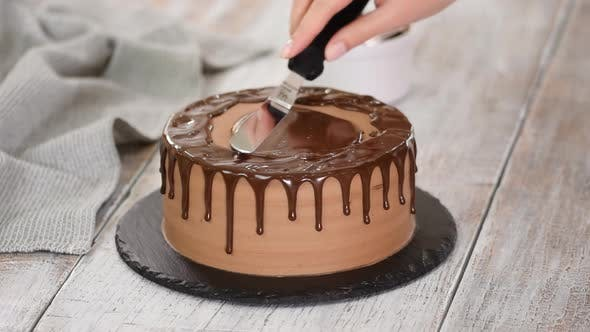 Thumbnail for Glazing chocolate cake with melted chocolate. Woman pouring chocolate over cake.