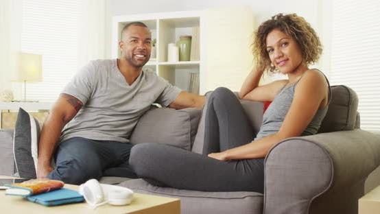 Thumbnail for Happy black couple sitting on couch smiling