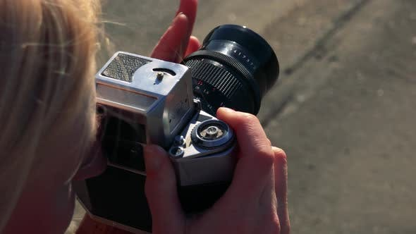 Thumbnail for A Blonde Woman Takes Photos with a Camera in a Street - Closeup From Above