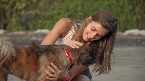 Thumbnail for Cheerful Woman Petting Dog and Jogging on Ocean Shore