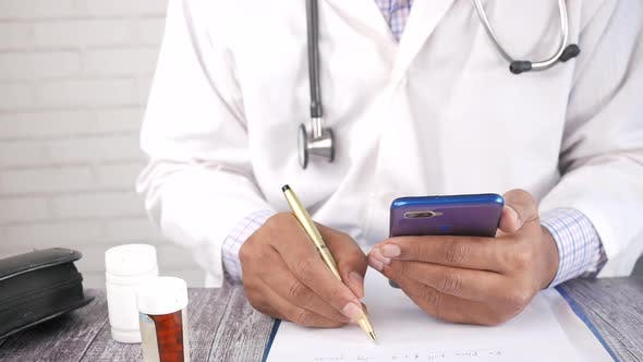 Doctor Hand Writing Prescription on Desk and Using Smart Phone