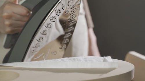 Eine Frau bügelt Kleidung mit einem Dampfbügeleisen auf einem Bügelbrett