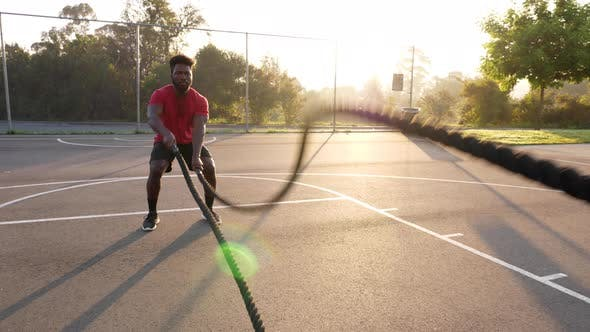 African American man working out with battle ropes