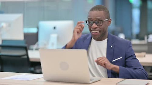 Successful African Businessman with Laptop Dancing at Work