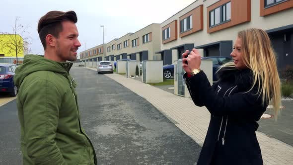 Thumbnail for An Attractive Man Poses for an Attractive Woman To Take a Picture of Him on an Empty Street