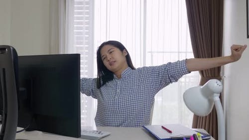 Middle-aged, long hair Asian woman stretching arms to relieve muscles pain.