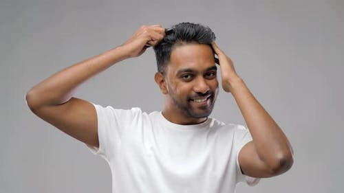 Happy Indian Man Brushing Hair with Comb 1