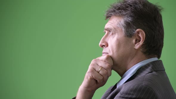 Mature Handsome Businessman Against Green Background