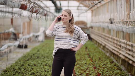 Thumbnail for Agriculture - Female Gardener Using Mobile Phone in Greenhouse