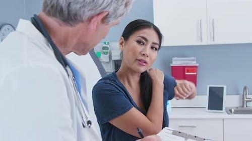 Japanische Frau erklärt Rotator Manschette Schulter Schmerzen zum Arzt in Prüfung Zimmer