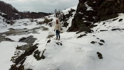A Tourist Girl in a Jacket Stands on the Slope of a Snowy Mountain in Nature