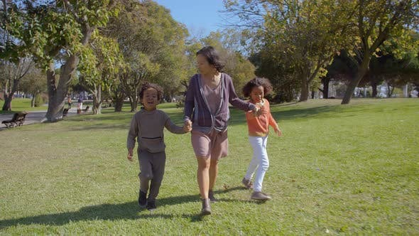 Thumbnail for Happy Asian Mother Holding Hands with African American Kids and Walking in Slow Motion