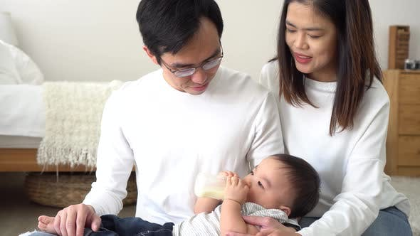 Asian Family of Young Father and Mother Feeding a Baby Boy From Milk Bottle