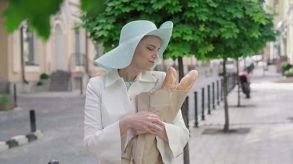 Thumbnail for Mittlerer Schuss der eleganten Frau reißen Stück Baguette und Lächeln in der Kamera. Porträt von attraktiven