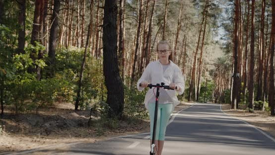 Blonde Child is Riding a Scooter in the Park