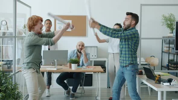 Slow Motion of Crazy Businessmen Fighting Paper Swords While Colleagues Cheering in Office