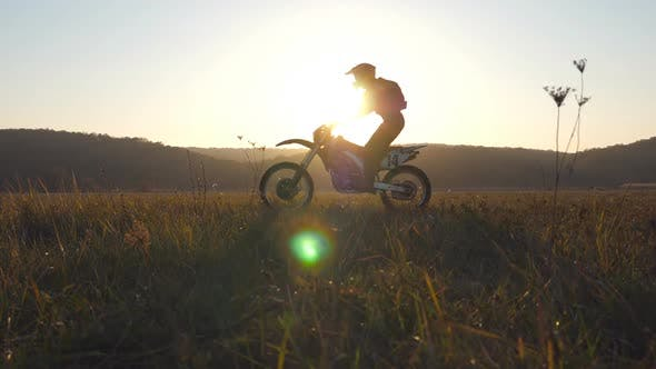 Thumbnail for Two Motorcyclists Passing Through Large Field with Beautiful Sunset at Background. Warm Summer Sun