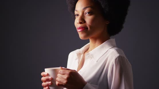 Black woman with afro holding cup of hot coffee and smiling