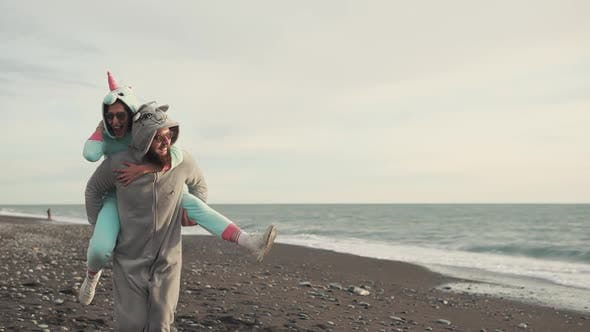 Thumbnail for Happy Spouses in Kigurumi Costumes Running on a Stone Beach Near the Sea