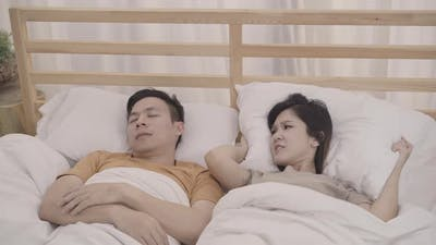 Asian couple wife annoyed Snore's husband when their sleep female insomnia and can't sleep.