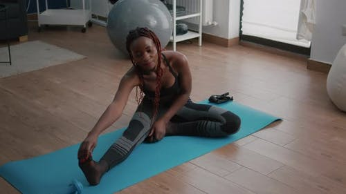 Flexible Fit Black Woman Doing Stretching Routine on Yoga Map