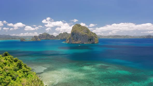 Thumbnail for Aerial Drone Circling Shot of Rocky Pinagbuyutan Island in Open Sea From the Distance. El Nido