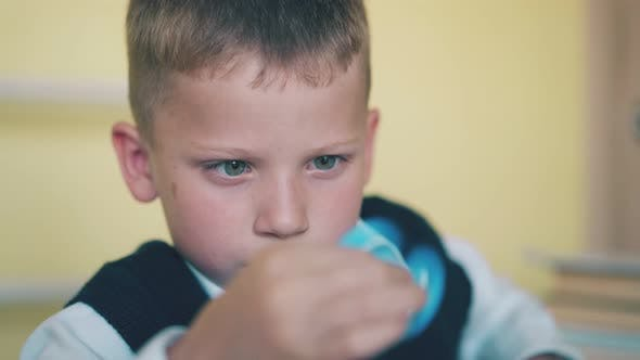 Little Boy Plays with Turning Toy at Break in Classroom