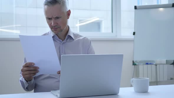 Thumbnail for Pensive Businessman Reading Papers