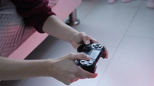 Hands holding controller playing video games