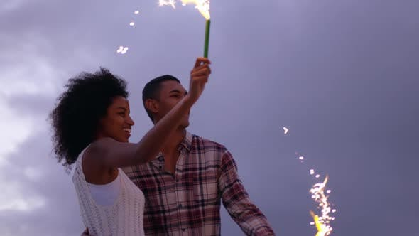 Thumbnail for Couple playing with sparklers on beach at dusk 4k