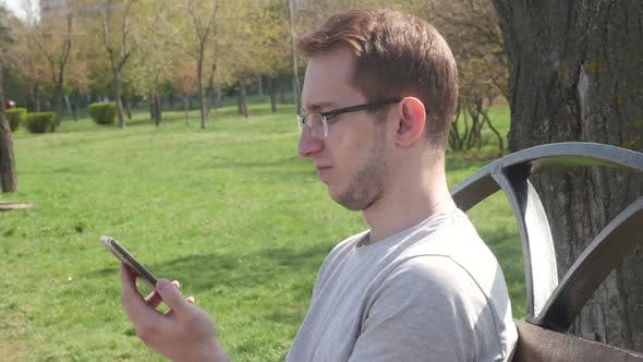 Thumbnail for Man In The Park Uses A Smartphone