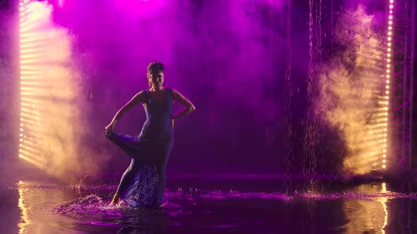 A Charming Middle Aged Woman Passionately Dances Flamenco Among Raindrops and Splashing Water,  Smoky