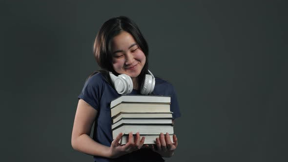 Thumbnail for Asian Student Girl with Headphones on Grey Background Holds Stack of Books