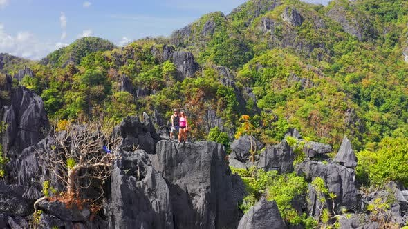 Thumbnail for Couple Family Traveling Together on Cliff Edge Taraw in El Nido, Philippines. Man and Woman