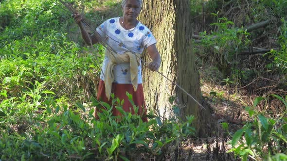 Thumbnail for Grey Haired Lady Gathers Wood in Shady Forest Slow Motion