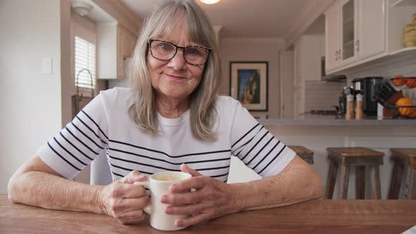 Thumbnail for Happy Senior woman looking at camera with her morning coffee at kitchen table