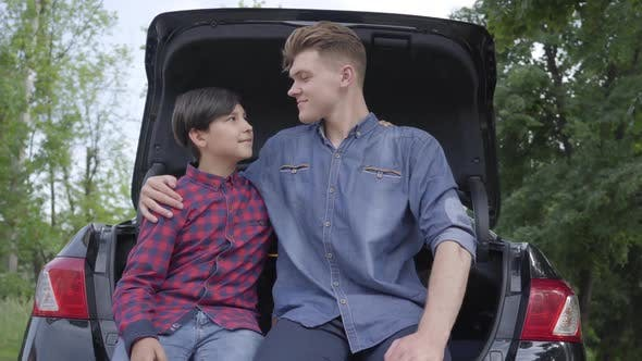 Thumbnail for Young Father and His Son Sitting on the Back of the Car Outdoors. The Man Hugging Boy, People