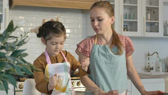 Thumbnail for Little Girl Adds Yolk While Mother Pours Flour To Cook Pie