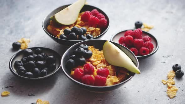 Thumbnail for Golden Cornflakes with Fresh Fruits of Raspberries Blueberries and Pear in Ceramic Bowl
