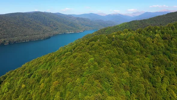 Thumbnail for Aerial view over mountain lake with turquoise water and green trees forest